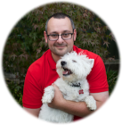 Guy wearing a red polo shirt holding his happy looking white dog.